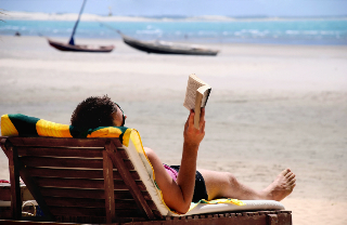 Photo of woman reading at the beach
